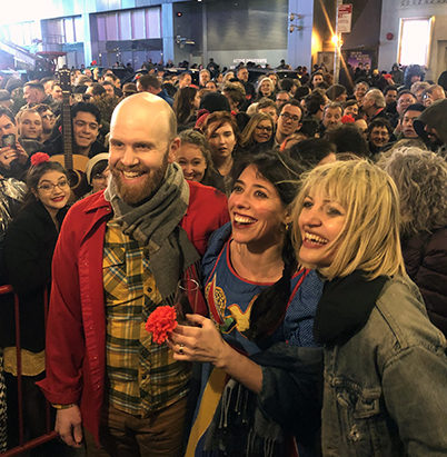 """Liam Robinson, Rachel Chavkin, and Anaïs Mitchell lead fans outside the """"Hadestown"""" stage door in a traditional Irish folksong"""